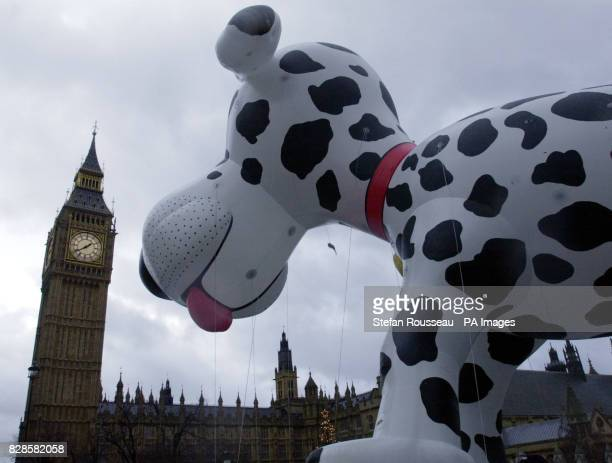 A giant inflatable dog appears to dwarf Big Ben in London during this year's New Year's Day parade More than 10000 performers endured a damp start to...