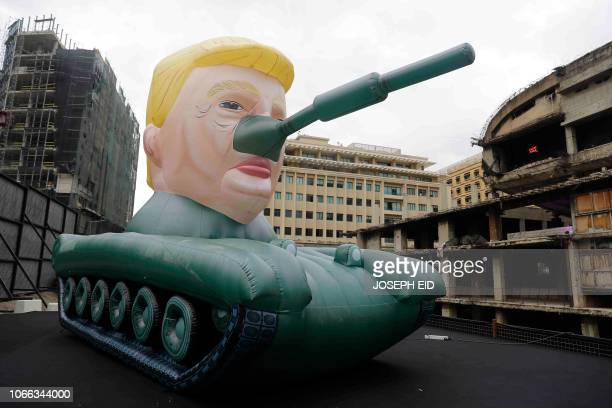 TOPSHOT A giant inflatable tank bearing the head of US President Donald Trump is displayed outside an art exhibition by an anonymous artist who goes...