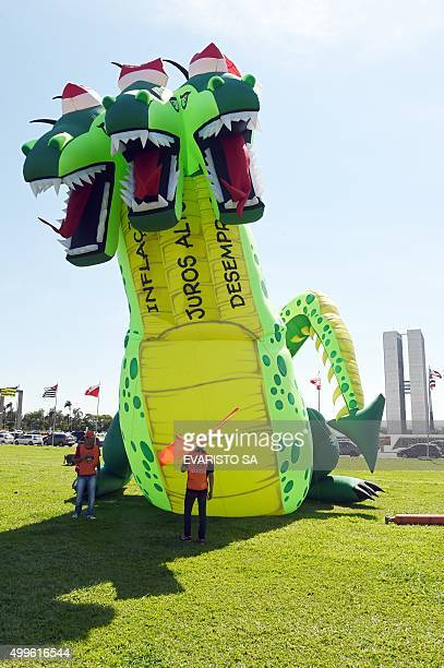 A giant inflatable threeheaded dragon doll representing inflation is seen in front of the National Congress during a protest by the Union Federation...