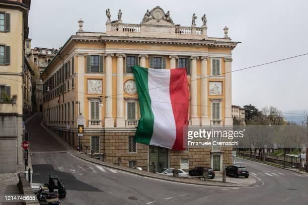 Giant Italian national flag is pictured hanging over the facade of Palazzo Medolago Albani on March 25, 2020 in Bergamo, near Milan, Italy. Bergamo...