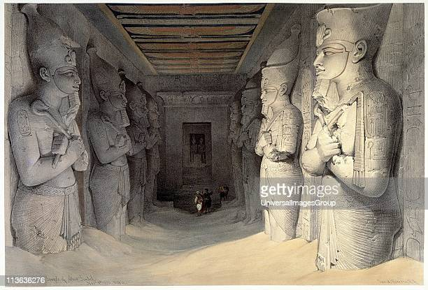 Giant limestone statues of Ramses II holding the crook and the flail symbols of kingship Temple of Ramses Abu Simbel On left each statue has...