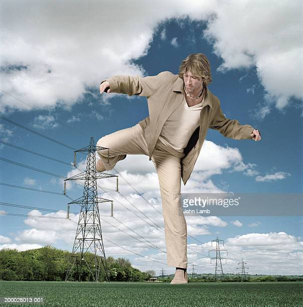giant man stepping over pylons in field (digital composite) - giantess stock photos and pictures