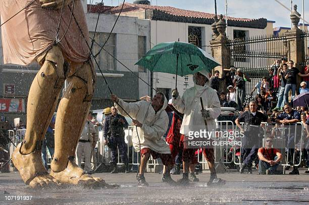 A giant marionette called 'Little Giant' of the French street theater company Royal de Luxe is operated by members of the company in Guadalajara...