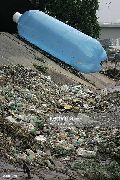 A giant mock plastic bottle lies on the bank of the highly polluted Tiete river in Sao Paulo Brazil 30 January 2008 as part of an experimental study...