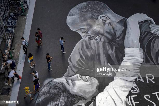 A giant mural of former NBA star Kobe Bryant and his daughter Gianna painted hours after their death is seen at a basketball court in a slum area on...
