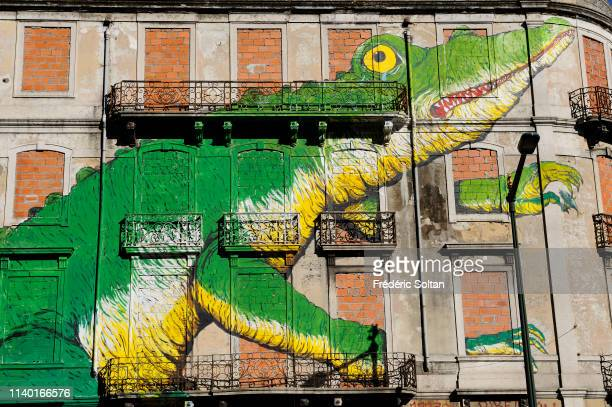 Giant mural painting in Lisbon painted by Portuguese artists Blu and OS Gemeos illustrating the emptied planet of its richnesses by the oil...