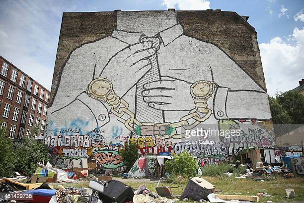A giant mural showing a figure wearing a tie and chained to two wristwatches looms over the Cuvrystrasse squat in Kreuzberg district on June 26 2014...