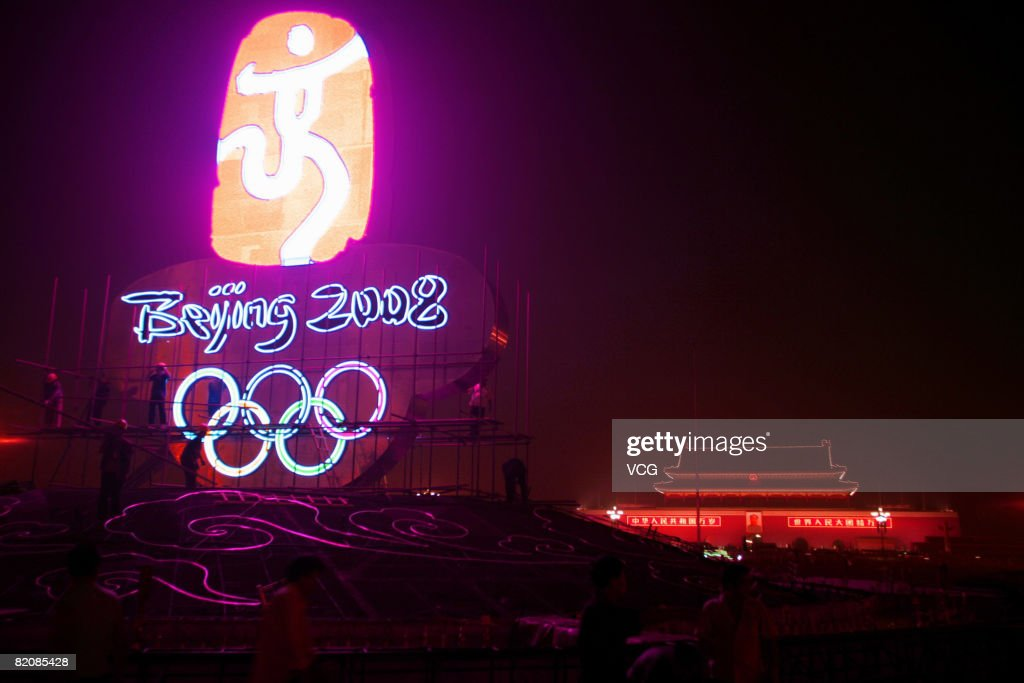A giant neon Beijing 2008 Olympic Games symbol with olympic rings, forming the centrepiece of a parterre, lights up Tiananmen Square while workers carry out finishing touches at night on July 27, 2008 in Beijing, China. The formal garden will remain on display nearly three months; throughout the Olympic Games, the Paralympic Games and China's National Day. The last parterre to be set up at Tiananmen Square was in 1986.