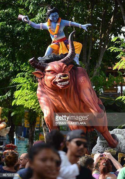 Giant 'Ogohogoh' effigies symbolising evil are led during a procession before they are burned in a ritual to purify worshippers from evil in Kuta on...