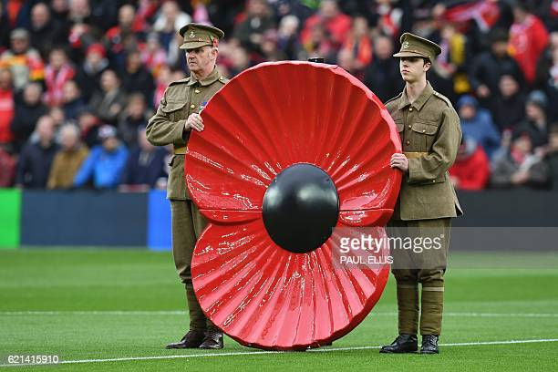 A giant poppy is displayed during a minute's silence in honour of Remembrance Day during the English Premier League football match between Liverpool...