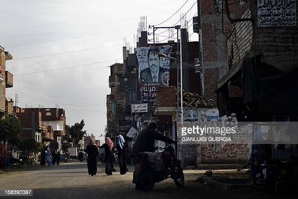 A giant portrait of Egyptian President Mohamed Morsi hangs from a building in his hometown Adwa in the Nile Delta on December 15 2012 Egypt's...