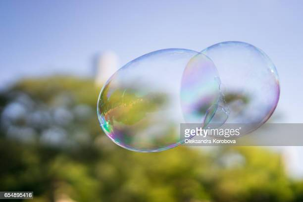 Giant rainbow soap bubbles floating in the summer air during a beautiful sunny day.