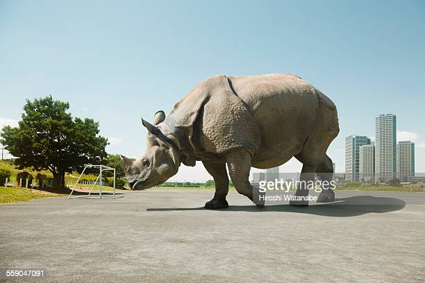 Giant rhinoceros walking on soccer ground