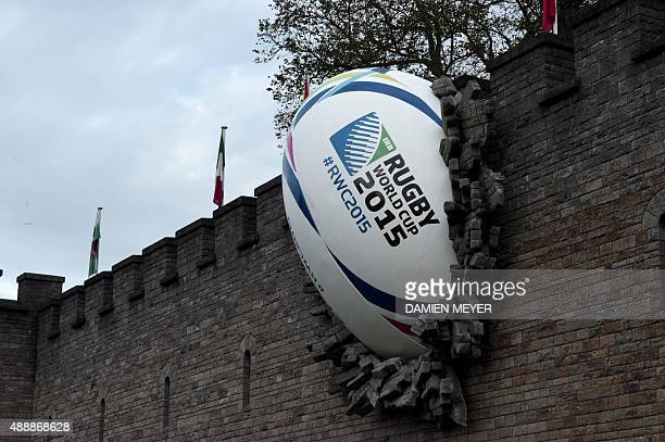 A giant rugby ball is pictured breaking through the wall of Cardiff castle on September 18 ahead of the 2015 Rugby Union World Cup AFP PHOTO / DAMIEN...