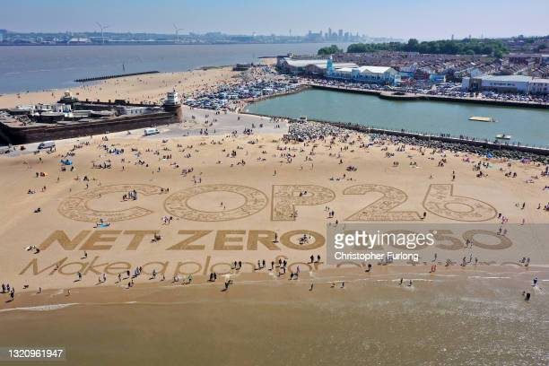 Giant sand art work adorns New Brighton Beach to to highlight global warming and the forthcoming Cop26 global climate conference on May 31, 2021 in...