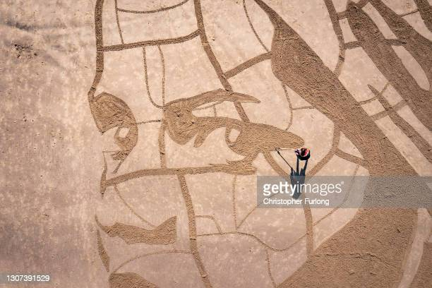 Giant sand portrait by WaterAid and artists Sand In Your Eye of Ansha, a 12-year-old from Frat in Ethiopia adorns Whitby Beach on March 15, 2021 in...