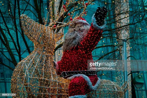 A giant Santa Claus figure riding a reindeer is seen in Berlin on December 24 2017 / AFP PHOTO / John MACDOUGALL