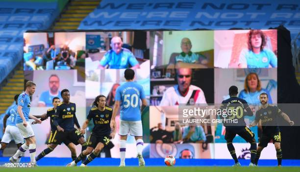 Giant screen display s Manchester City fans as they watch the match on their computers during the English Premier League football match between...
