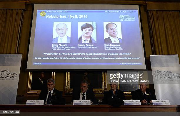 A giant screen displays the images of Japaneseborn researchers Isamu Akasaki Hiroshi Amano and Shuji Nakamura as Nobel Committee for Physics chairman...