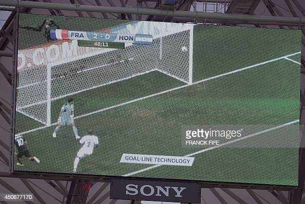 A giant screen in the stadium shows an action replay of France's Karim Benzemas shot using the new goal line technology during a Group E football...