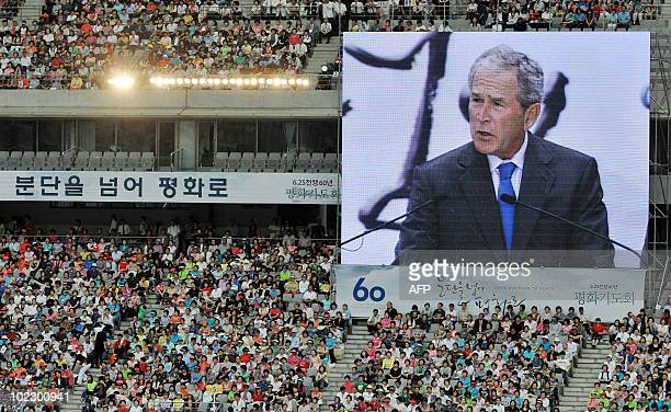 A giant screen shows former US president George W Bush delivering a speech at a prayer meeting at Sangam World Cup Stadium in Seoul on June 22 to...