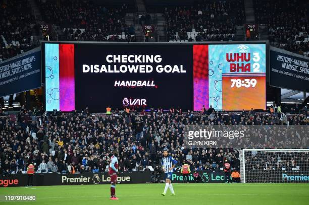 Giant screen shows the VAR being checked for a disallowed goal, which was overturned allowing during Brighton's English striker Glenn Murray to...