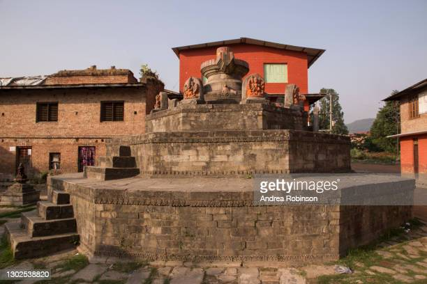 giant shiva lingam which is the largest in nepal and various stone carvings and idols surrounding the pillar in the hanuman ghat area of bhaktapur in the kathmandu valley, nepal. - shiva lingam stock pictures, royalty-free photos & images