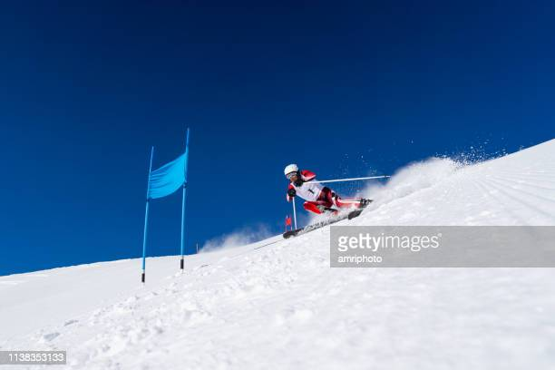 giant slalom ski race one male skier at blue door - competizione foto e immagini stock