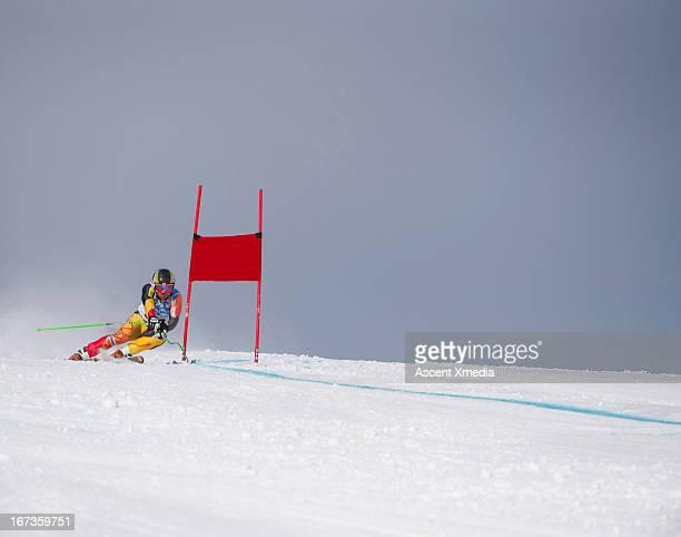 giant slalom skier rounds gate at high speed - ski slalom stock-fotos und bilder
