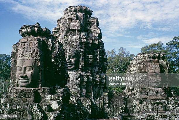 Giant smiling statues in the Bayon temple in the ruins of Angkor Thom ancient capital of the Khmer empire in Cambodia circa 1970