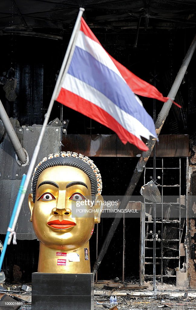 A giant statue of a head stands next to Thai national flag at the site of a fire at Thailand's biggest shopping mall - Central World - after it was set ablaze the day before following an army assault on an anti-government protest site in downtown Bangkok on May 20, 2010. Thailand's biggest shopping mall faces collapse after it was set ablaze by enraged protesters in the wake of an army offensive to shut down an anti-government rally, police said.