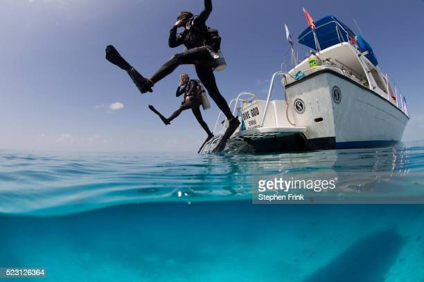 giant stride entry into calm ocean. - scuba diving stock pictures, royalty-free photos & images