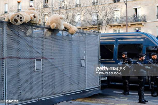 Giant teddy bears have been placed on anti-riot fences as riot mobile gendarmes stand at a crossroad of the avenue des Gobelins in Paris on January...