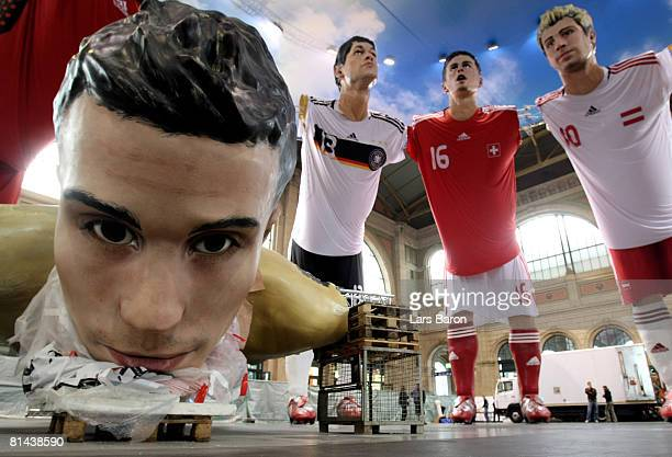 Giant three dimensional display of Robin von Persie of Netherlands lies on the ground in front of three dimensional displays of Michael Ballack of...
