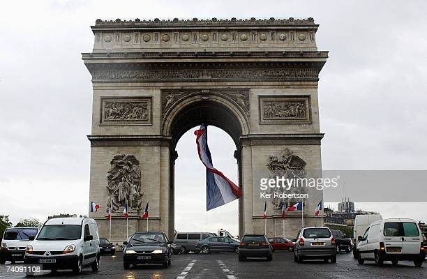 Giant Tricolor flag flies at the Arc de Triomphe as a stage set up during the Second Round of the French Presidential Elections is dismantled on May...