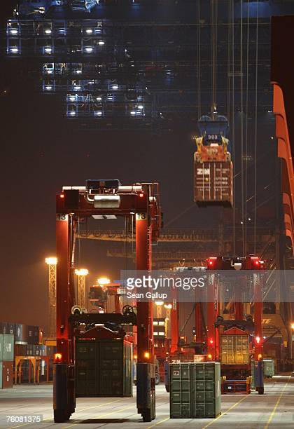 Giant vehicles used for picking up and tranfering shipping containers help load a ship at the main container port August 13 2007 in Hamburg Germany...