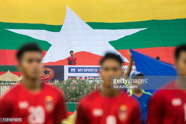 A giant version of the Myanmar national flag is displayed as the team stands at attention for their national anthem before the Tokyo 2020 Olympic...