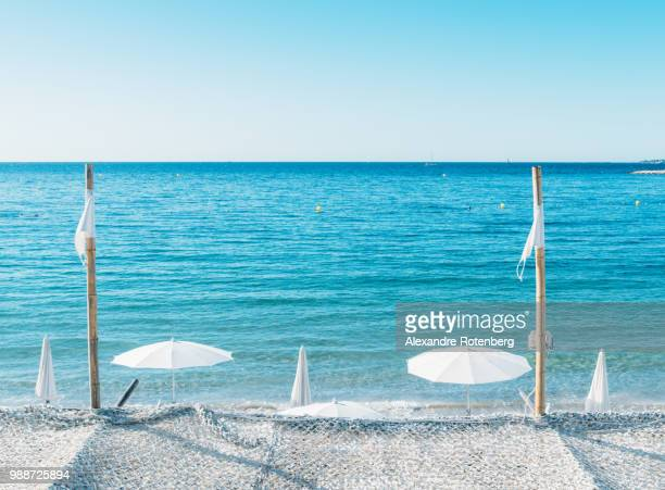 giant white beach umbrella next to the ocean against a blue sky in juan les pins, cote d'azur, provence, france, mediterranean, europe - alexandre coste foto e immagini stock