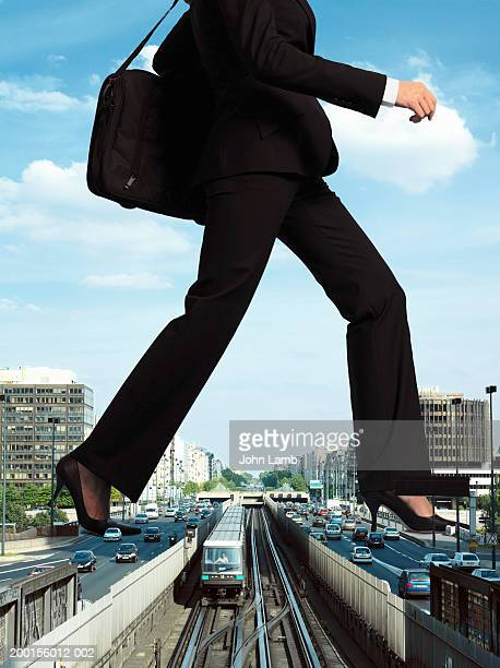 giant woman stepping over train on tracks (digital composite) - striding stock pictures, royalty-free photos & images