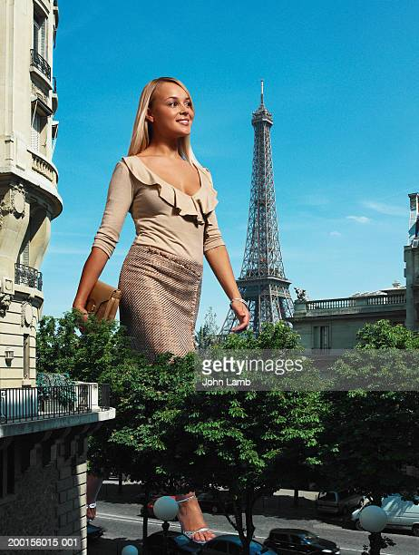 Giant woman walking on road past Eiffel Tower (Digital Composite)