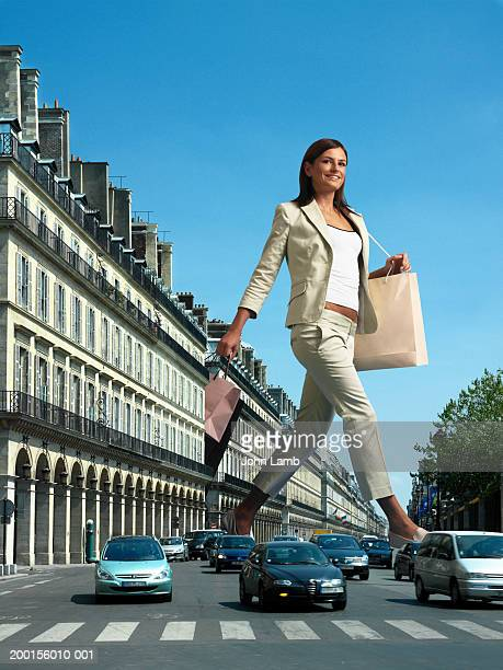 giant woman with shopping bags crossing busy road (digital composite) - giants stock photos and pictures