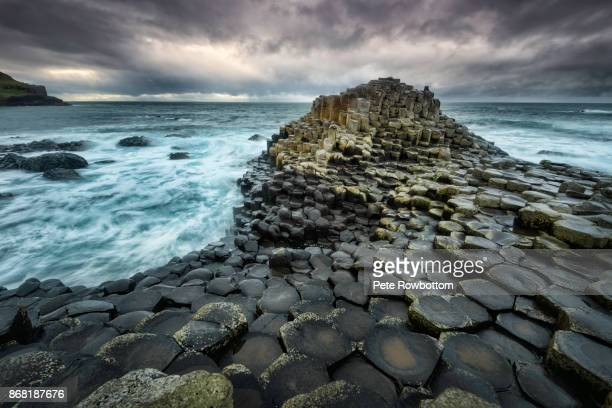 giants causeway in a storm - county antrim stock pictures, royalty-free photos & images