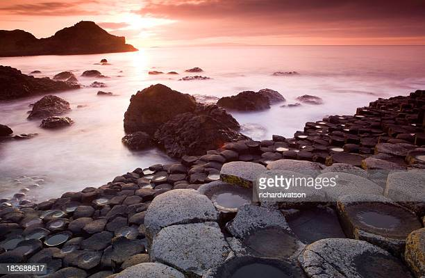 A Giants Causeway with fog on the ground during sunrise