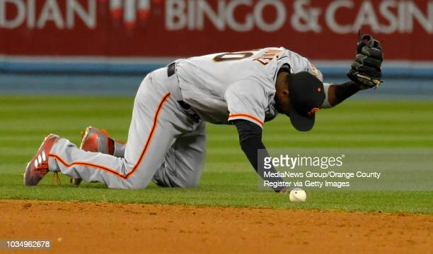 Giants' Eduardo Nunez slams his glove to the ground after beting bobbling the ball on an Adrian Gonzalez hit in Los Angeles on Monday May 1...