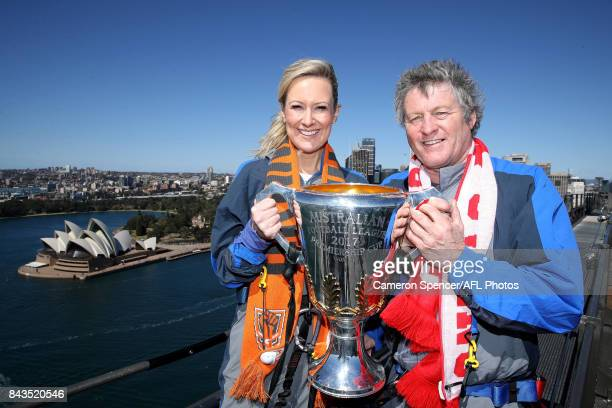 Giants fan Melissa Doyle and Sydney Swans fan Peter Phelps pose with the AFL Premiership Cup on top of the Sydney Harbour Bridge on September 7 2017...