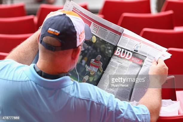 Giants fan reads a newspaper story about Lance Franklin of the Swans before the round one AFL match between the Greater Western Sydney Giants and the...
