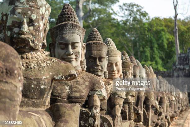 giants in front gate of angkor thom, in angkor wat, siem reap in cambodia. - khmer art stock photos and pictures
