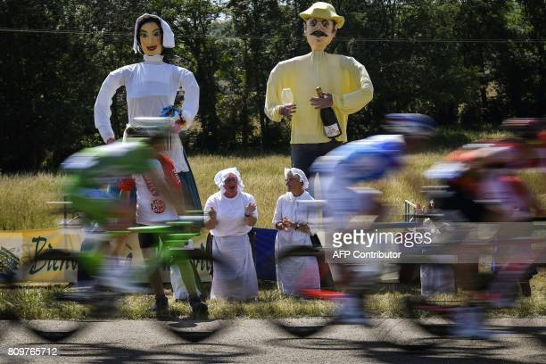 TOPSHOT Giants statues are pictured along the road as woman cheer during the 216 km sixth stage of the 104th edition of the Tour de France cycling...