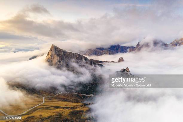 giau pass, ra gusela, cinque torri dolomiti alps covered by clouds, aerial view, italy - atmospheric mood stock pictures, royalty-free photos & images