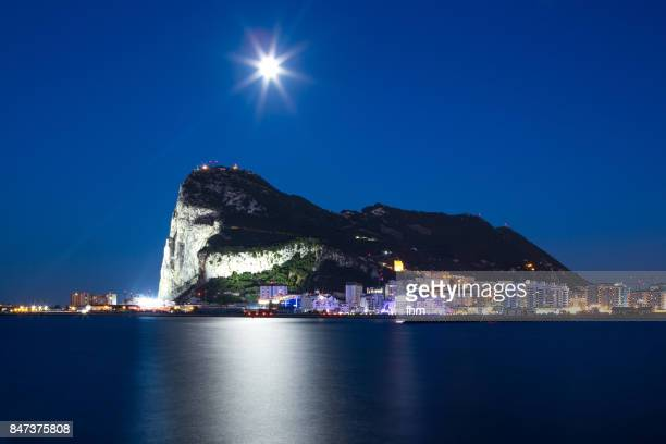gibraltar at blue hour with moon - upper rock, seen from spanish side la linea de la conception - rock of gibraltar stock photos and pictures